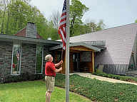 Bill raising the flag at the inn to start summer